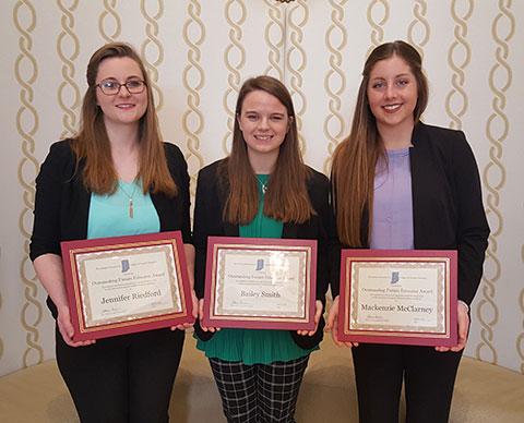 Three girls holding awards