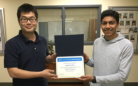Two students holding an award