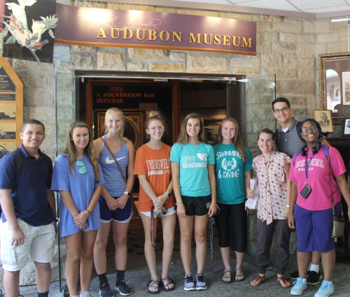 Students standing in front of the Audubon Museum entrance sign