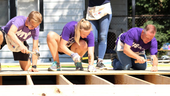 President Pietruszkiewicz and UE students hammer nails into a floorboard