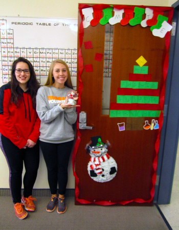 Chemistry students Lauren Roberts and Maegen Kincanon standing by Christmas decorated door.