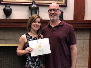 Tyra Baker holding Award Certificate